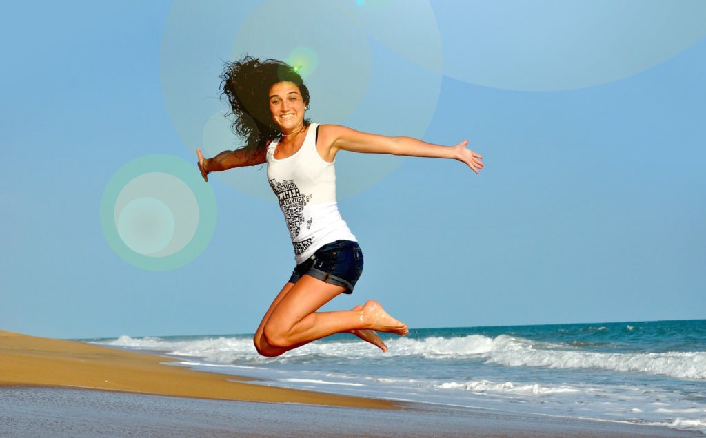 girl jumping for joy on the beach with hair all over the place